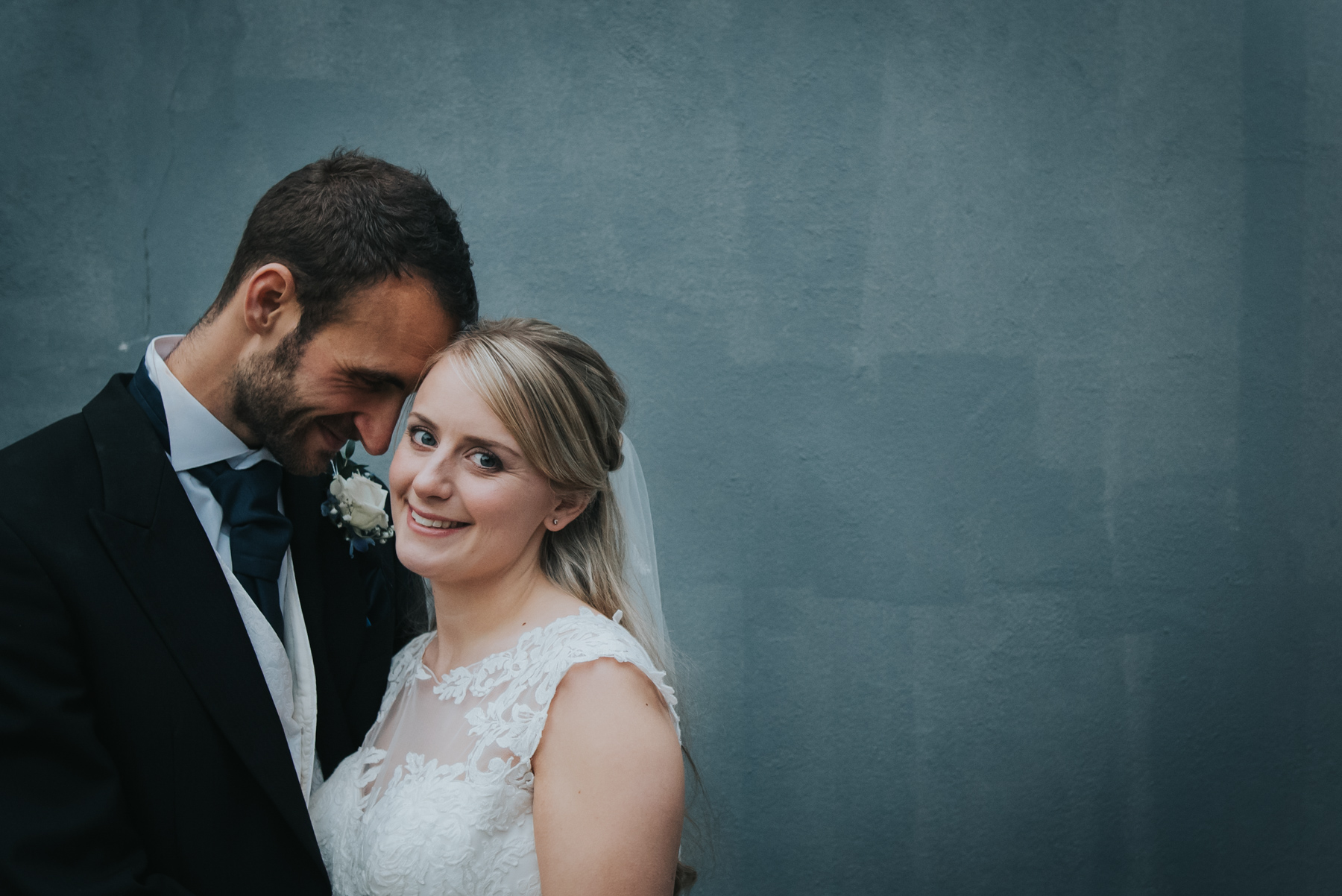 bride and groom against grey wall