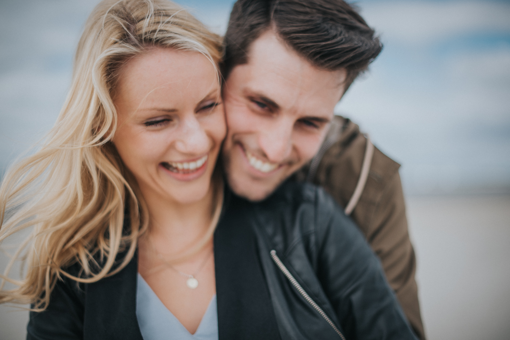 beautiful couple laughing on the beach shallow focus