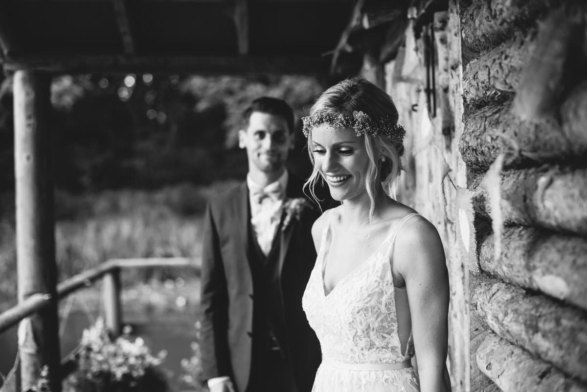 black and white bride and groom by log cabin