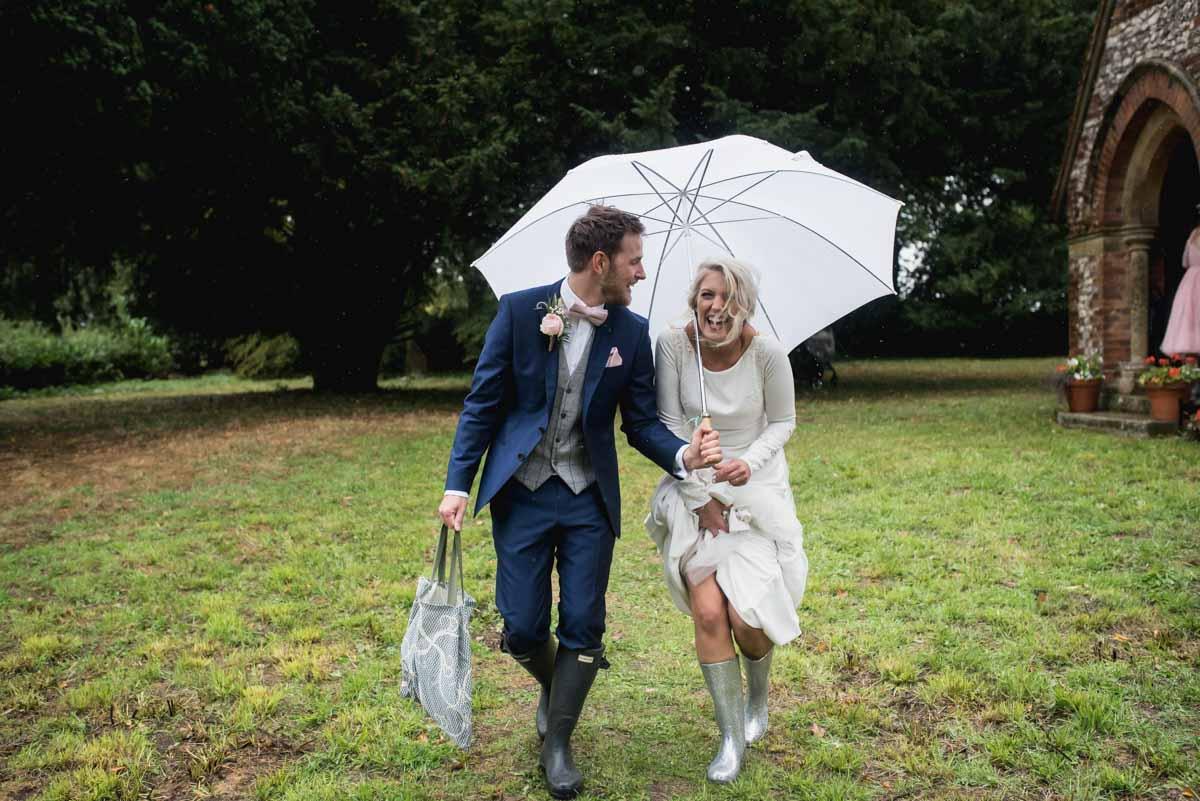 raining wedding bride and groom in wellies laughing