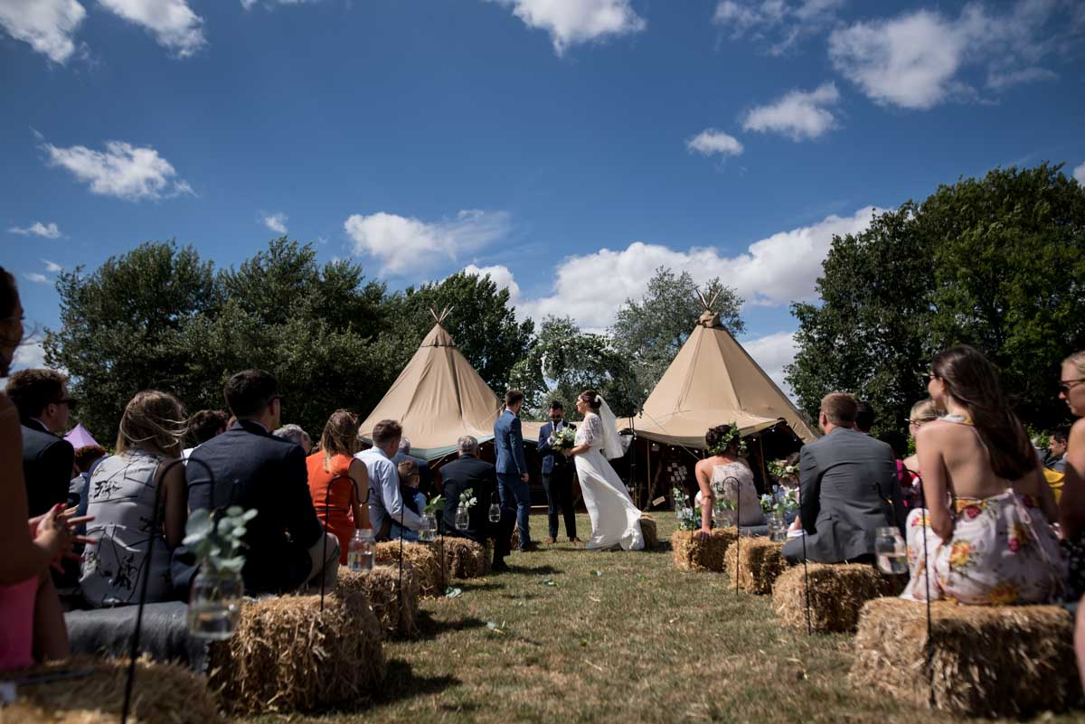 couple getting married in front of a tipi in a vineyard