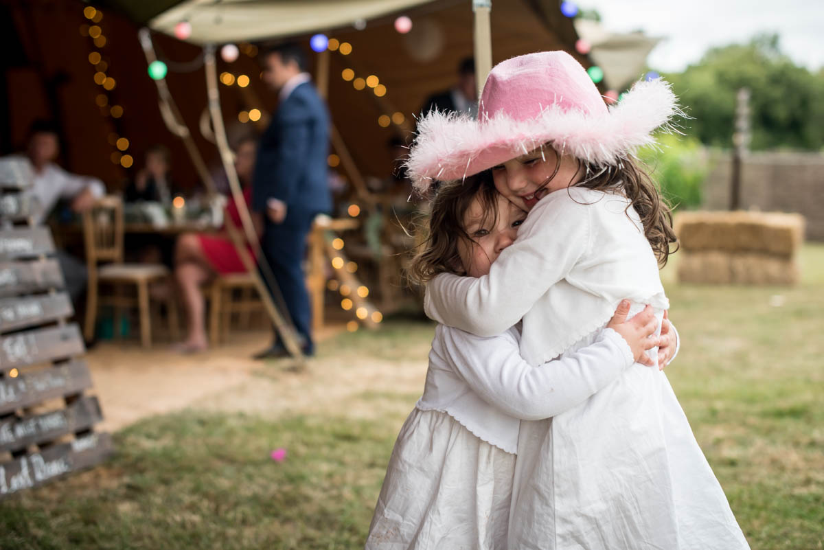 two kids cuddling at a wedding