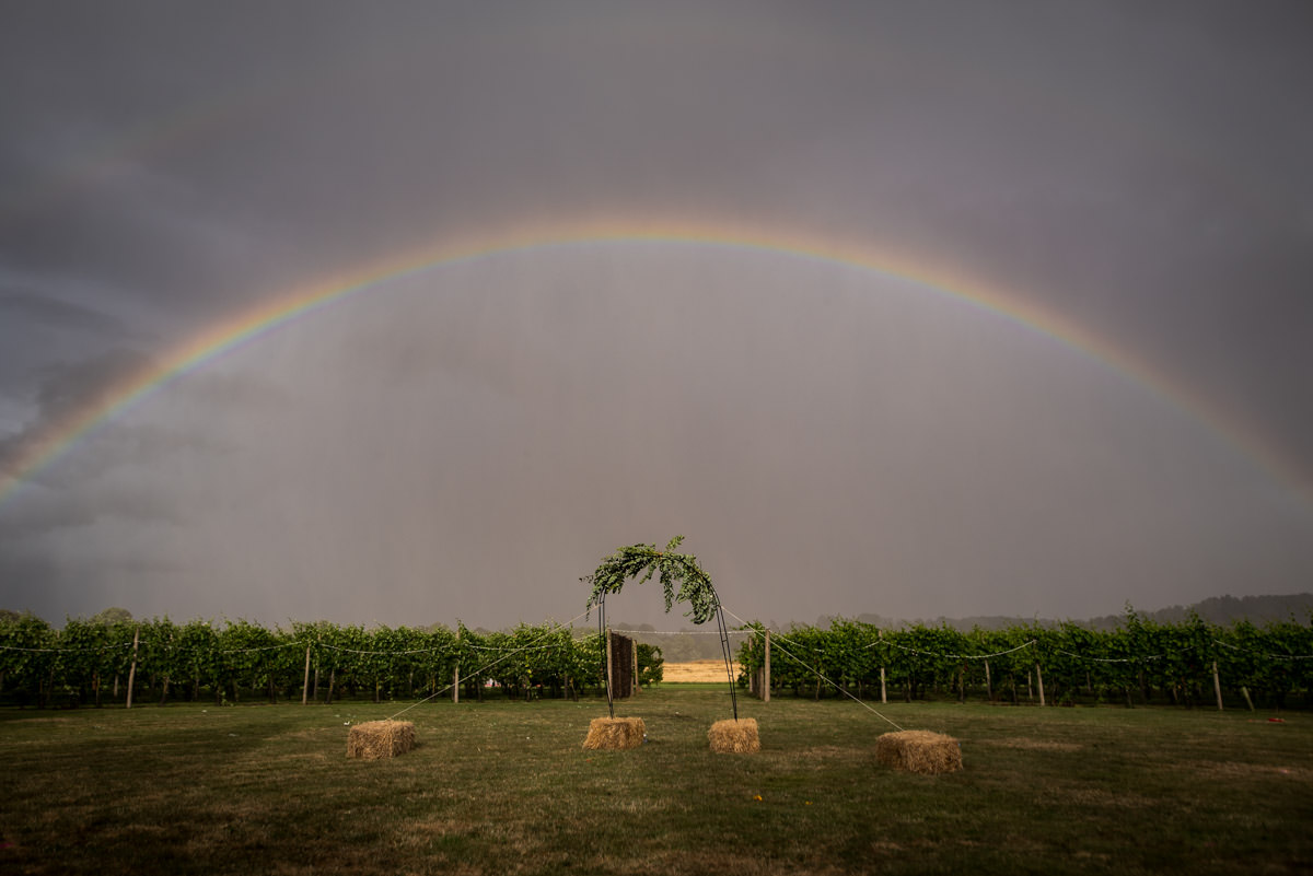 rainbow over outdoor wedding arch