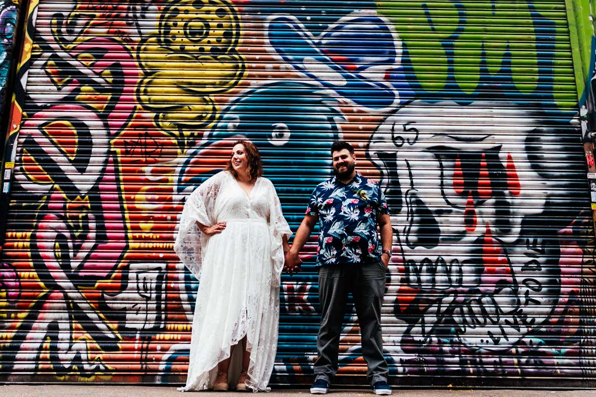 alternative wedding couple in front of graffiti wall