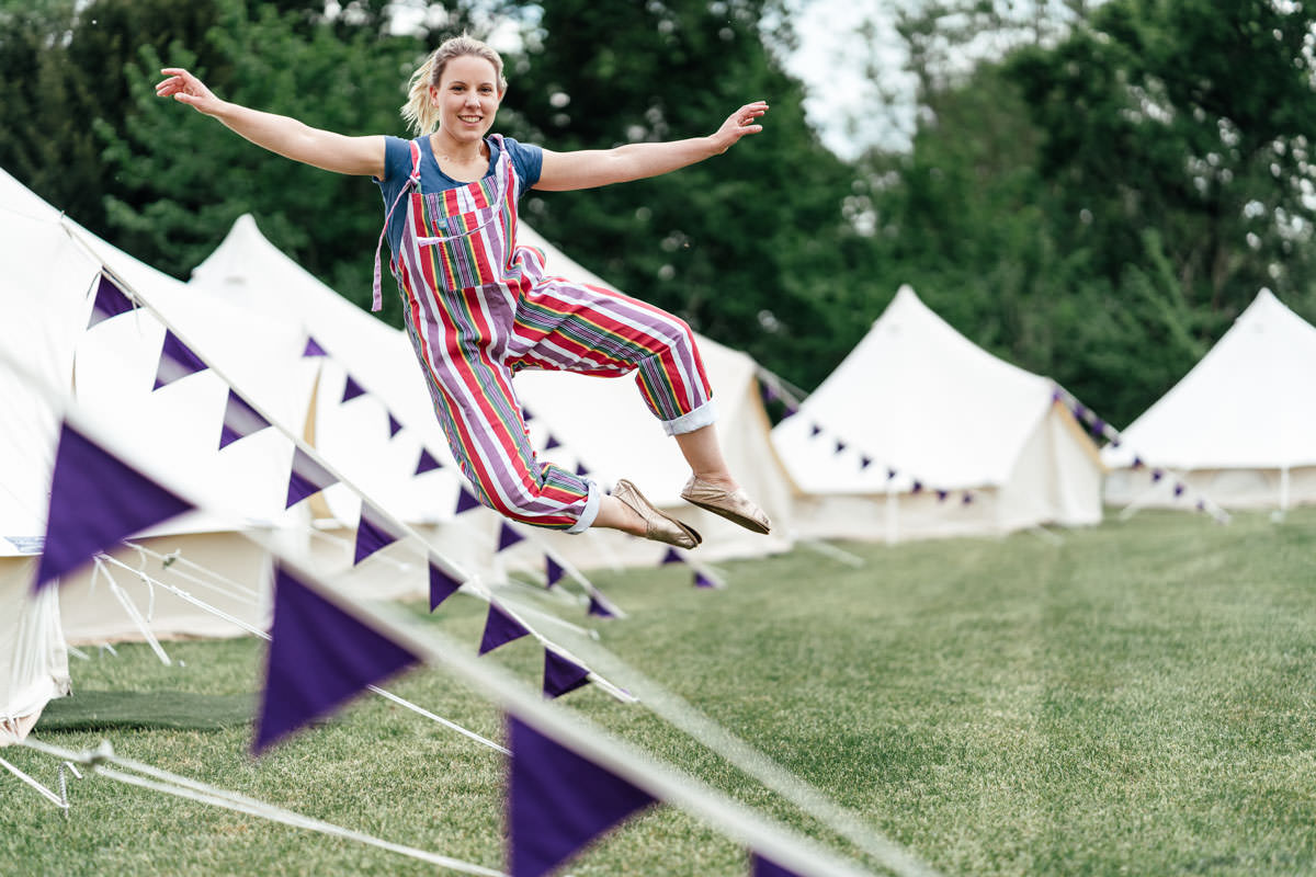 girl jumping by bell tents